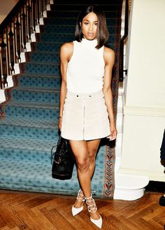 Ciara wears a high neck white knit top, suede zip-up miniskirt, black satchel, and white lace-up suede heels