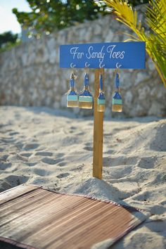 Cute beach wedding ceremony idea - custom paintbrushes for brushing the sand off guests feet.