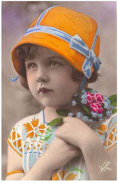 Little girl in orange bonnet with flowers