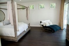 Bedroom: Minimalist Master Bedroom With Chaise Lounge. minimalist bedroom. unfinished wood canopy bed. white bedding. blue lounging chair. metal round table. hard wood flooring.