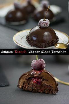 Ein cremiges Schokoladen Mousse Törtchen mit fruchtiger Kirsch Füllung, schokoladigem Boden und einem Überzug aus glänzender dunkler Mirror Glaze.