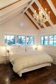 Love the vaulted wood paneled ceiling with the exposed white beams and chandelier (maybe a fan instead?). Also like the placement of the bed with the vault of the ceiling.