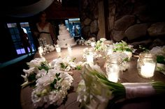 Wedding cake table with mason jar candles and white flower clusters