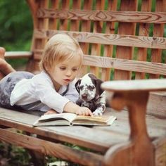 A little toddler teaching her puppy how to read! He's looking down on the page too!... This is just too cute!