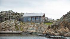 KORTSIDEN: Slik ser hytta ut når man ankommer brygga. Den korte delen ligger vendt mot sjøen. Med lerk i kledningen og stein som forsterkende elementer har arkitekten lykkes med å legge hytta inn i landskapet. Foto: Espen Grønli