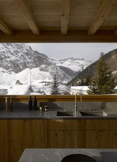 Rothaus | Jonathan Tuckey Design, Andermatt, Switzerland. The kitchen is finished with larch joinery and a honed granite worktop.