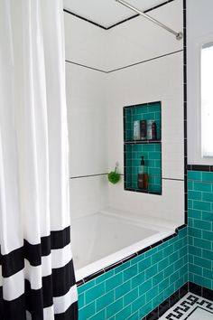 A tiled alcove keeps must-haves handy in the shower and soaking tub. The striped shower curtain adds another layer of black and white charm to this retro-inspired design.