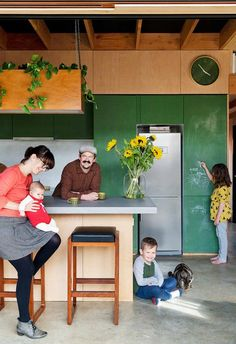 The kitchen cabinets are painted in a green chalkboard paint to encourage the children's creativity. Polished concrete flooring is matched with the concrete kitchen island benchtop, with the base clad in plywood. Plywood Kitchen, Concrete Kitchen, Painting Concrete, Stained Concrete, Concrete Lamp, Bungalows, Green Plywood, Plywood Floors, Laminate Flooring