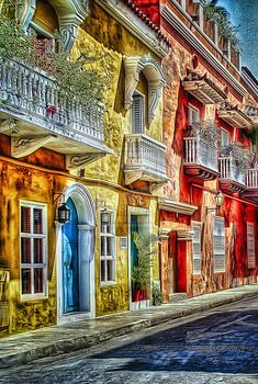<3 Colorful balconies line the streets of Cartagena, Colombia. Visitors can take tours of the old city and walk on top of the wall which surrounds the entire city!