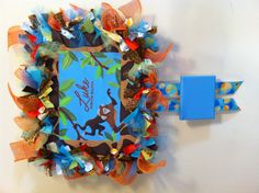 Birth announcement wreath for hospital door. Little boy, jungle theme.  Ribbon wreath inspired edge of canvas: staple two rows of string around edge of canvas then tie strips of ribbon to the string.