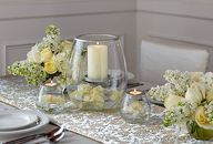 Elegant centerpiece with hurricane, candles, yellow and white flowers
