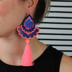 The patterned coral red fabric used in the small teardrop shape in this earring was once a skirt, which i rescued from a charity shop sale rail.  After falling in love with the fabric i decided to use it as a starting point for a new collection of textile jewellery. I added neon orange, coral, navy, lilac and glittery blue fabrics, tassels, vinyl and gems to create a bold and colourful range that could be worn to add a splash of colour and fun to any outfit. Textile Jewelry, Jewellery, Coral Navy, Mollie Makes, Shop Sale, Charity Shop, Recycled Fabric, Blue Fabric, Vintage Prints