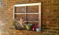 Patio window with shelf...bought the old window frame with glass still intact at a yard sale for 2 dollars.  I added a simple wooden shelf to the bottom and then hung onto my porch brick wall.  How fun!