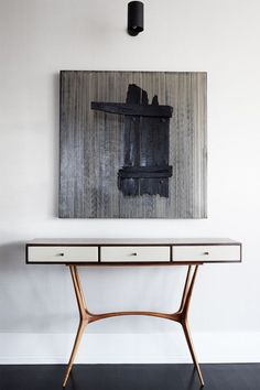Console by Guiseppe Scapinelli ca.1950s, artwork titled Vibracion Toro by Jesus Soto and wall sconce by Serge Mouille. / Elle Decor
