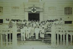 """Personeel van het Surinaamsche Roode Kruis op het bordes van het """"Nepveu-huis"""" aan de Gravenstraat. Hier was ook gevestigd Loge Concordia. Datum: Locatie: Gravenstraat, Paramaribo, Suriname Vervaardiger: Inv. Nr.: 35-18 Fotoarchief Stichting Surinaams Museum"""