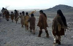 A reenactment of hunter-gatherers walking with crops they've gathered at the end of the ice age.