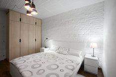 Ložnice je jediná místnost, která zůstala na svém místě a v původním rozměru, zařídili ji postelí a nočními stolky z kolekce Malm (6290 Kč a 799 Kč, Ikea). Také tady nechali vyniknout původní cihly