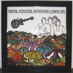 The Monkees. Background single piece of white glass. Title, logo, drawing of group drawn on computer and printed on special contact paper. Design was transferred to the glass, then sandblasted and painted black. Flowers are free form, joined together to make a separate piece. Bits of clear glass were siliconed under where the flowers are attached so that the flowers stand away from the rest of the piece and also allow white background to show through..