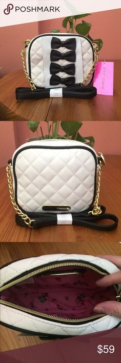 """Black Tie Chic Crossbody Bag Adorable bows adorn the front of this spacious Crossbody bag. Features include partial chain shoulder strap and zip top closure. No interior or exterior pockets. Bag will arrive with cardboard bow protectors as seen in photos. Approximately 6"""" H x 7"""" X 2"""" D without strap. Please ask if you have questions. Betsey Johnson Bags Crossbody Bags"""