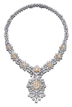 A DIAMOND AND YELLOW DIAMOND PENDENT NECKLACE. The detachable pendant set with a cushion-shaped yellow diamond weighing 20.92 carats in a vari-cut diamond cluster surround with marquise-cut and pear-shaped fringe suspended from a series of seven cushion-shaped yellow diamond and vari-cut diamond flowerhead clusters, the yellow diamonds weighing 1.72, 1.84, 3.97, 4.11, 4.44, 4.53 and 5.79 carats, to the vari-cut backchain, mounted in 18 yellow and white gold, 45.0 cm.
