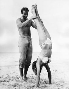 Sean Connery holds Ursula Andress while she does a handstand on the set of Dr. No, 1962