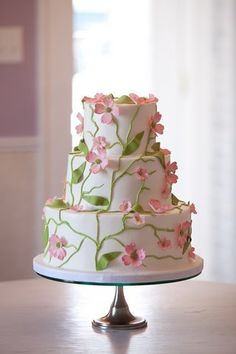 beautiful white tier cake with pink flowers, vines and leaves