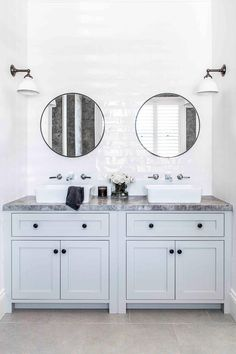 Double vanity bathroom with round mirrors and light blue cabinetry in modern farmhouse in the New South Wales Southern Highlands. Marble Benchtop, Kitchen Benchtops, Antique White Usa, Hampton Style Bathrooms, Tumbled Marble Tile, Cottage Bath, Cozy Cottage, Bathroom Renos, Vanity Bathroom