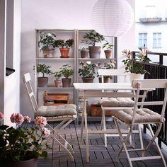 Parveke, jossa valkoiset taittotuolit ja pöytä sekä teräshyllyjä.