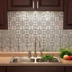 PVC tile with an aluminum finish that you can purchase in large tiles, and then just attach to your old backsplash, from 'Home Depot'.