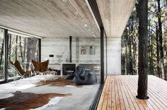 This bold but natural house design works wonderfully with its woody surroundings and the lake lapping at the shoreline just steps away, putting raw earth and modern architecture within arm's reach - now, this is our idea of an ideal cottage getaway! The massive sliding glass walls provide a barely-there boundary between the wild and our creature comforts, a line that is further blurred by the use of an earthy palette inside.