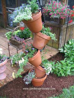 I love this stacked container garden. This is made by simply threading a length of metal rebar through the holes of the pots.   (this same look is really pretty when planting with vinca and other flowing flowers)