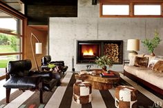 In the living room, smooth concrete walls surround a steel firebox devised by the architects. Sergio Rodrigues lounge chairs and a Michael Wilson lamp, all from JF Chen, face a free-form wood low table by Cristiano do Valle from Espasso and vintage cowhide stools from Hollywood at Home. The rosewood-and-leather sofa and Navajo-inspired rug were designed by Stuart.