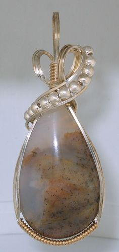 Plume Agate Pendant from Delta, Utah wrapped in Sterling Silver and accented with Sterling Silver beads and gold filled wire. Nice wire wrapping design.