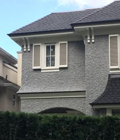 Grey stucco, white windows and trim, black roof & gutters. Heavy slop stucco dash.