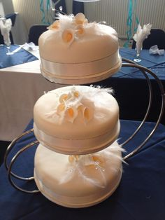 3 tier cream cake with lilies and feathers on swan stand