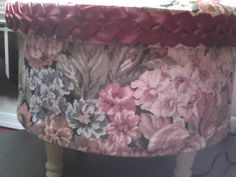 """Foot stool made from large cheese wheel box, covered in fabric, added painted wood legs and added slip knot braid with 1/2"""" satin ribbon."""