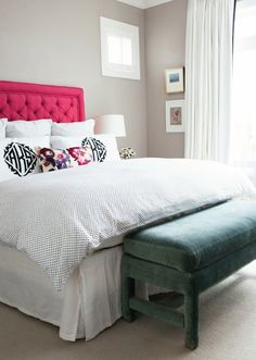 Glamorous bedroom features hot pink, tufted headboard on queen bed dressed in silver polka dot bedding and monogrammed shams as well as floral lumbar pillow alongisde green velvet bench placed at foot of bed.
