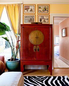 Red Chinese moon cabinet, yellow walls Benjamin Moore Dalila 319, zebra rug Cost Plus. Leslie Lundgren Design.
