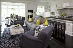 Martha O'Hara Interiors    Wide open living room - kitchen design with pigeon gray 3 cushion sofa, blue gray linen chairs with nailhead trim, blue gray damask rug & pillows, bright yellow pillows and lamp and natural linen ottoman table