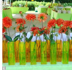 Orange dahlias in alternating orange or green vases added a punch of color to the escort card display.