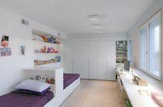 Aménagés dans la longueur de la chambre, les lits sont séparés par une petite étagère permettant à chaque enfant de...