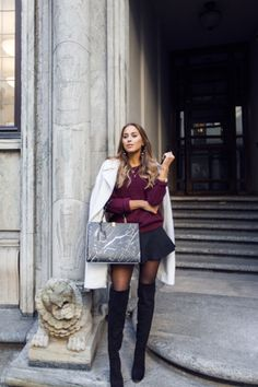 Kenza Zouiten wears her over the knee boots with a black mini skirt and plum coloured knit sweater. Boots: Novita from Scoritt, Coat: Asos, Bag: Balenciaga, Skirt/Sweater: Old.