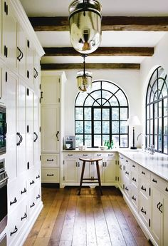 Really like the steel windows with the black hardware. This kitchen has so much light! From Design Chic