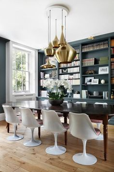 Love the combination of mid-century modern chairs, traditional shelving and the hot dark green color walls which is predicated to be hot in 2017