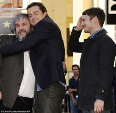 Still close: Lord of the Rings' director Peter Jackson gets a hug from Orlando as Elijah l...