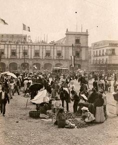 Plaza del Zocalo en la Ciudad de Mexico, fiestas del 16 de Septiembre, se observa el paso de un tranvia. Al fondo la calle de Madero, antes Plateros. Imagen del principios del siglo XX