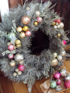 Lets take a pool noodle, old tinsel garland and older Christmas balls. Got this covered. Glittery Wreath