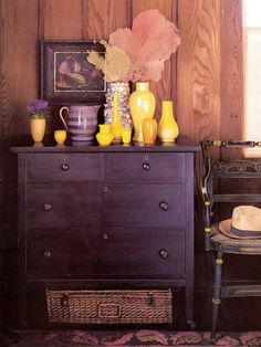 Dark furniture, like this purple dresser, can bring a room the security and warmth of deep colours without overpowering it. Bright yellow vessels holding an assortment of dried coral bring levity and lightness to the wood-panelled room.