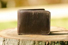 """saddleback """"Thick, full-grain leather with a pigskin interior. This wallet is tough and still has a wonderful leather smell after a year of accidental liquid contact (Alcohol, beer and alcohol, rubbing to name a few.) The Saddleback arrived stiff and rough on touch, but over the course of a year the leather has developed a smooth surface with a variety of markings made from daily use."""""""