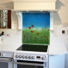With a clear blue sky and an abstract field of grass, the design of this bespoke splashback from Silverdale, Lancashire certainly makes for an appropriate setting to host a whole variety of life. Wildflowers of all shapes, sizes and colours grow from the bottom of the piece to blossom and shine in the foreground.